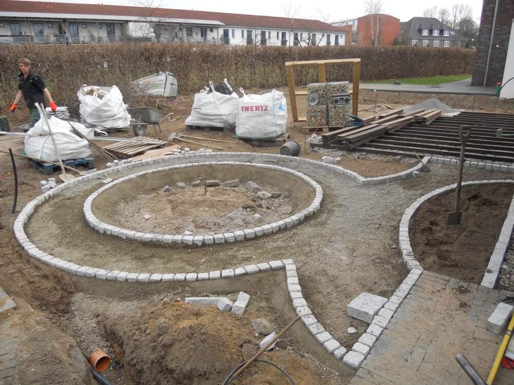 Im Hausgarten werden die Einfassungen der Wege und der Kräuterspirale verlegt