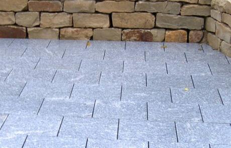 Sitzplatz aus Granitplatten mit Natursteinmauer