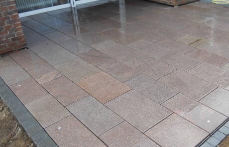 rote Granitplatten mit einer Bänderung aus Basaltpflaster