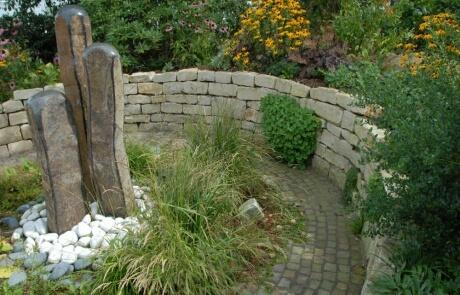 Natursteinmauer mit Polsterstauden bepflanzt