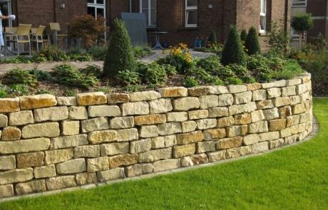 Natursteinmauer als Stützmauerwerk im Garten