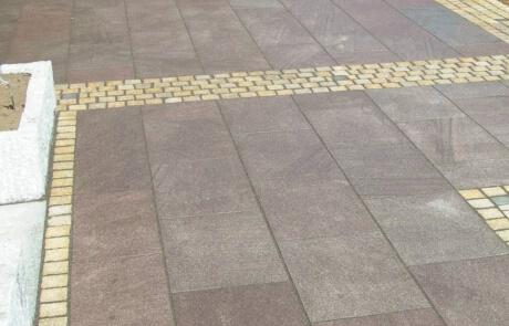 Terrasse aus roten Granit Natursteinplatten mit einer Bänderung aus gelben Natursteinpflaster